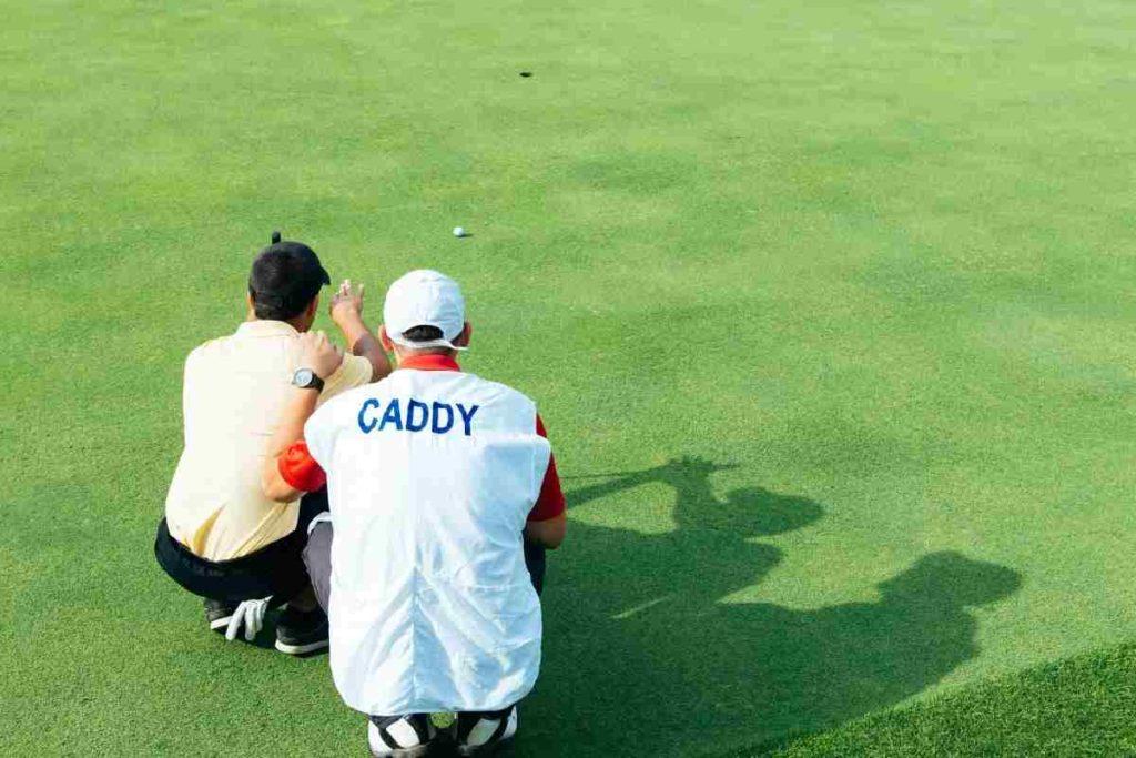 golf caddy helping golfer read a putt