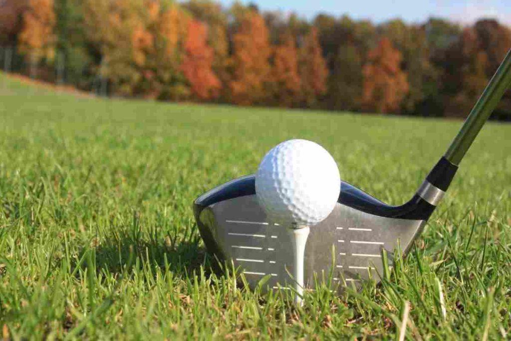 golf driver hitting ball on a tee