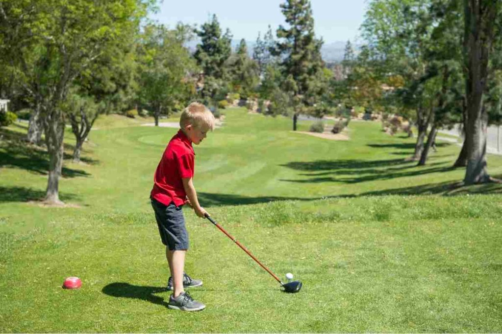 junior golfer driving the ball