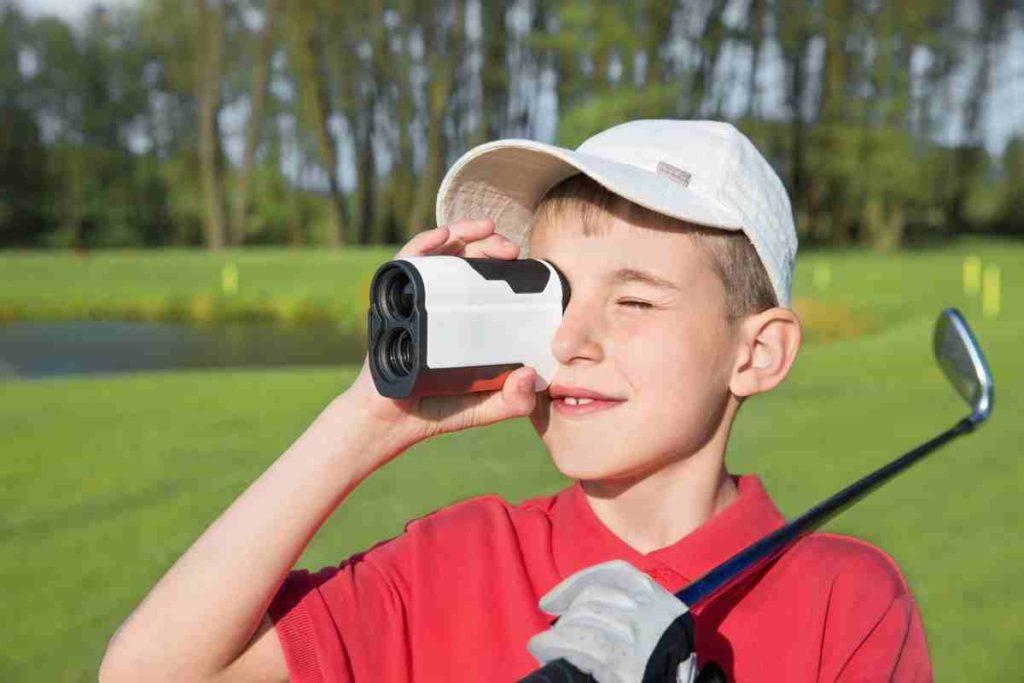 junior golfer using rangefinder on the golf course